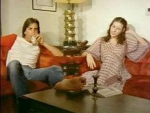 Секс-ретро дамы и молодого мужчины на красном диване